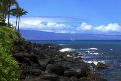 Sailboat and Lanai. Sailboat off the rocky coast of Maui with Lanai in the background Stock Images