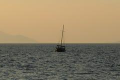 Sailboat leaving port against the horizon. Stock Image