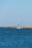 Sailboat with a lighthouse on the rocks Royalty Free Stock Photos