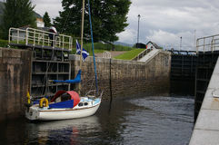 A sailboat through a loch. A sailboat going up a canal through a loch stock images