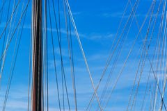 Sailboat mast and ropes in harbor against blue sky. Summer holiday vacation abstract background Stock Images