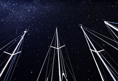 Sailboat mast on starry sky background. Night travel on luxury water transport, marina in nightime, bright stars on dark sky Stock Photo