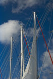 Sailboat masts. Against blue cloudy sky stock image