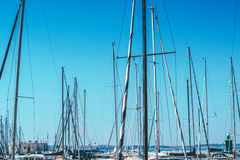 Sailboat masts in harbor against blue sky Stock Photos