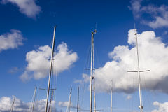 Sailboat masts. Some sailboat masts on a blue sky with clouds background Stock Images