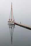Sailboat  mirrors in a foggy  Holandsfjord Stock Image