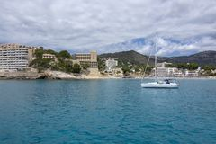Sailboat moored in Cala Fornells turquoise water stock photography