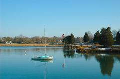 A sailboat moored in a calm bay Royalty Free Stock Photos
