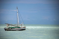 Sailboat moored in the silty waters of the Caribbean, Belize. Royalty Free Stock Images