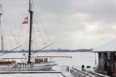 A sailboat at a mooring, Ontario lake, Toronto. A white sailboat with two flags of Canada and the city of Toronto at a dock of Ontario lake, Toronto. There is a Royalty Free Stock Photos