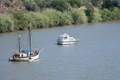Sailboat and motorboat moored on Rio Guadiana royalty free stock image
