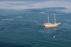 Sailboat and motorboat in sea. Sailboat at anchor on calm sea with lowered sails and small motorboat approaches the sailboat, shot from above, with copyspace Stock Photography