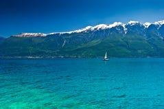 Sailboat on Mountain lake. In cold tones. Lago di Garda, Trentino, Italy Royalty Free Stock Photos