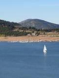 Sailboat on a Mountain Lake. A sailboat cruises a mountain lake on a beautiful sunny day stock photo