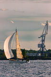 Sailboat moving past the cargo crane. In evening, Latvia stock photos