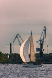 Sailboat moving past the cargo cranes. In evening, Latvia Royalty Free Stock Image