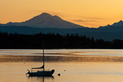 Sailboat and Mt. Baker. A sailboat during a dramatic sunrise anchors in Hales Pass in front of the active volcano Mt. Baker in the Puget Sound area of western Stock Images