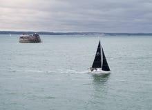 Sailboat navigating stormy waters. Sailboat navigating through stormy waters Royalty Free Stock Photography