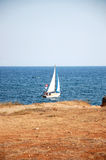 The sailboat. Near the coastline at sunny summer day Royalty Free Stock Images
