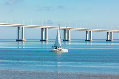 A Sailboat near a Long Bridge Royalty Free Stock Photos