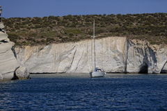 Sailboat near Milos cliffs Stock Photos