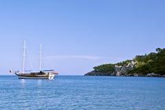 A sailboat near rocky coast. A sailboat with lowered sail near a rocky coast Stock Image
