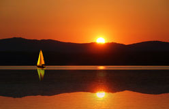Sailboat no por do sol Vela do veleiro fora no por do sol no lago Foto de Stock Royalty Free