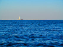 Sailboat in the ocean. Blue water and red boat with white sails Royalty Free Stock Photos