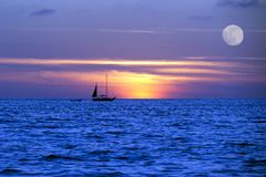 Sailboat Ocean Moon LightNight  Journey. A sailboat moves across the ocean on it's journey lighted by the moon light and the setting sun Stock Images