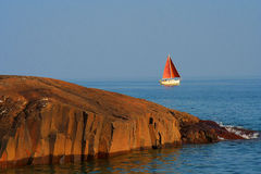 Sailboat off the coast of Lake Superior Minnesota. Sailboat passing by the rocky coast of Lake Superior in Minnesota Royalty Free Stock Image
