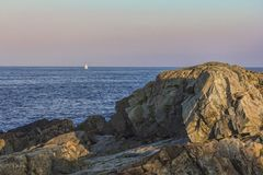 Sailboat off rocky shore at sunset Stock Images
