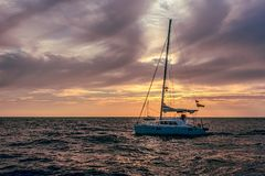 Sailboat on open sea during sunset under cloudy skies. Sailboat on open sea during sunset under cloudy orange skies Royalty Free Stock Photography