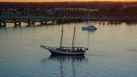 Sailboat with passengers sailing by city bay on a river  at beautiful sunset stock video