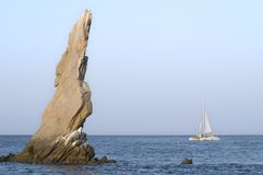 Sailboat passes Neptune's Finger. A catamaran sails past the rock formation known as Neptune's Finger, near Lands End in Cabo San Lucas, Mexico Stock Photo