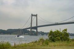 Sailboat Passing a Bridge Royalty Free Stock Photos