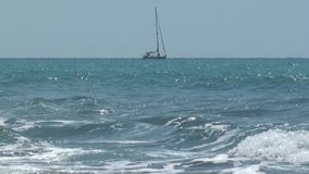 A sailboat passing in the wavy sea stock footage