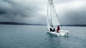 Sailboat passing by in the wide sea with two sailor onboard. Shot of a sailing regatta stock video footage