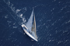 Sailboat In The Peaceful Blue Ocean. Top view of a sailboat in the peaceful blue ocean stock image