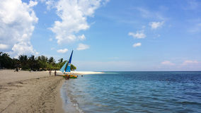 Sailboat and pedal boat on sandy tropical beach Royalty Free Stock Images