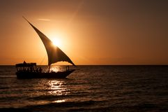 Silhouette of a sailboat at sunset in a quiet ocean stock image