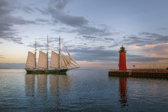 Sailboat and Red Lighthouse on Lake Michigan in Milwaukee, Wisconsin. At sunset with beautiful cloudy skies stock images