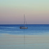 Sailboat reflected on sea water Royalty Free Stock Photos