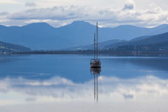 Sailboat reflecting in calm waters of Huon River, Tasmania Royalty Free Stock Images