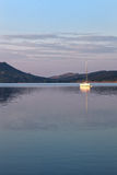 A sailboat reflecting in the lake at sunrise Royalty Free Stock Images