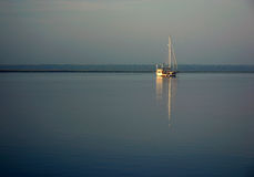Sailboat reflection. Sailboat reflecting on the surface of the water Royalty Free Stock Image
