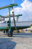 Sailboat in for repair in sling of travel lift boat moving machi Stock Photos