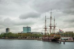 Sailboat replica called Amsterdam moored next to the National Maritime Museum in Amsterdam. Famous for its huge cultural activity, graceful canals and bridges Royalty Free Stock Image