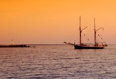 Sailboat returning to docks. After sunset Stock Images