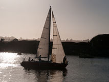 Sailboat returning to the marina at sunset. The crew preparing to lower the sails Stock Photo