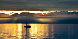 Sailboat and Rising Sun. A sailboat silhouetted against the Chablais Alps at Lake Geneva, Switzerland during sunrise in winter Royalty Free Stock Photo